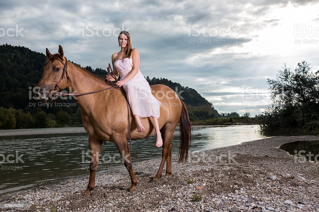 Woman riding brown horse bareback by river stock photo