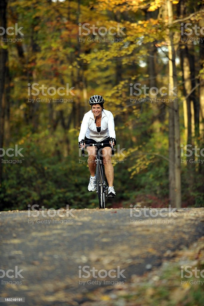 Woman riding her bike in the fall. royalty-free stock photo