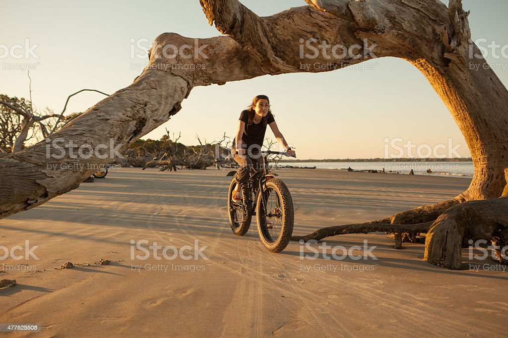Woman riding her fatbike along a beach on the ocean stock photo
