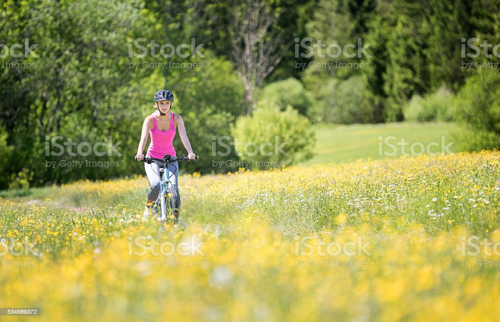 Woman riding her Mountainbike on a Trail, Fields of Flowers stock photo