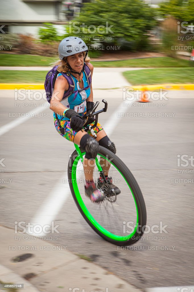 Woman riding her unicycle at a criterium competition stock photo