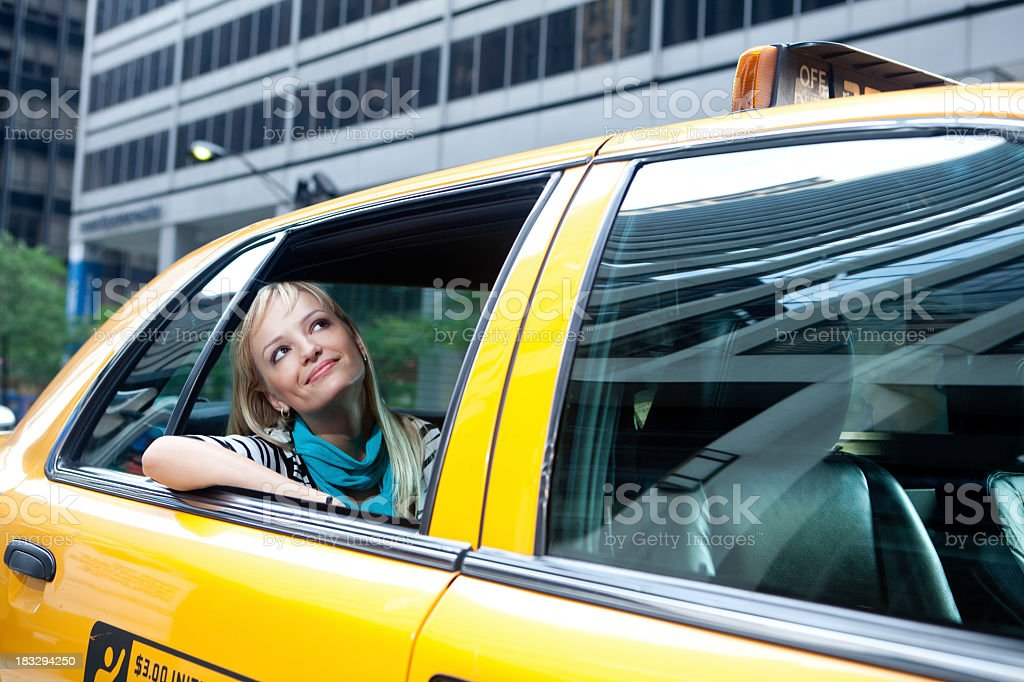 Woman riding in a yellow New York City cab admiring the city royalty-free stock photo
