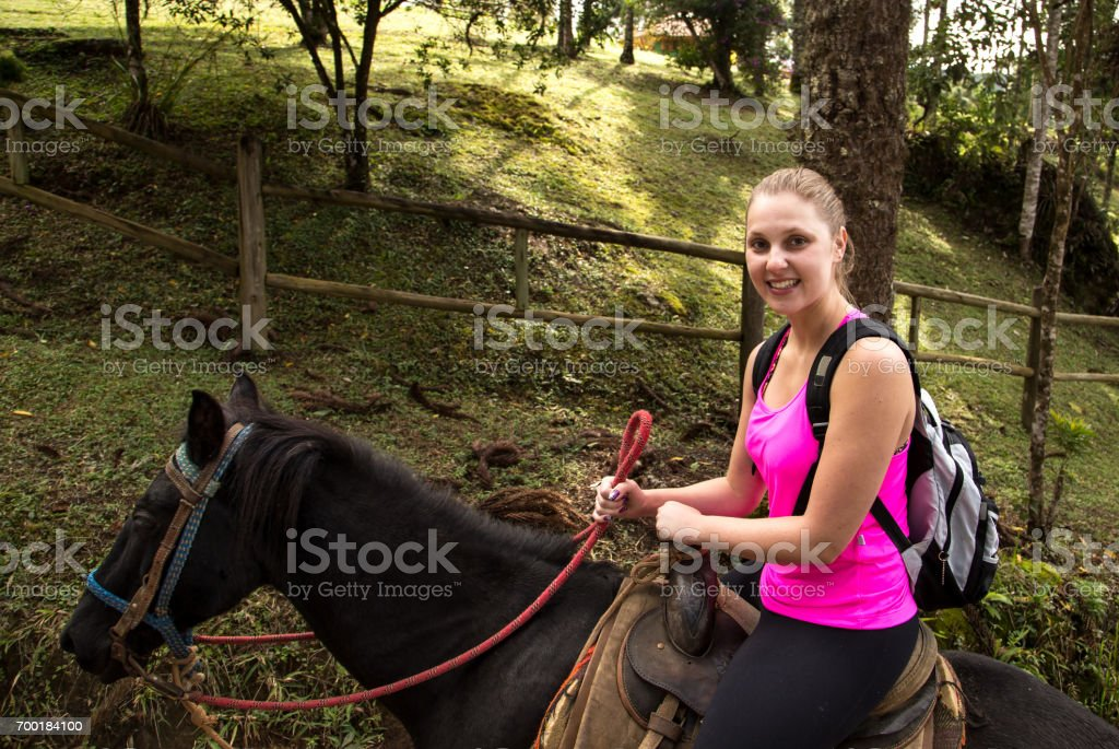 Woman riding on a brown horse stock photo