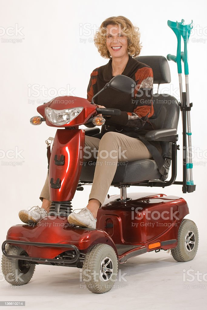 Woman riding on red mobility scooter with crutches stock photo