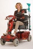 Woman riding on red mobility scooter with crutches