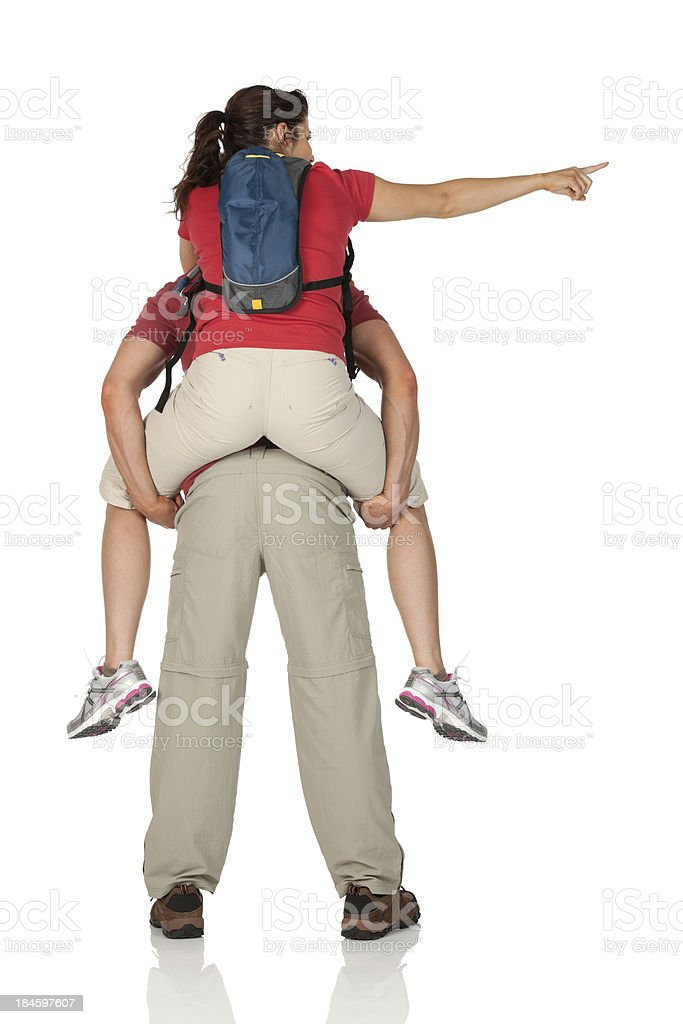 Woman riding piggyback on a man's shoulders stock photo