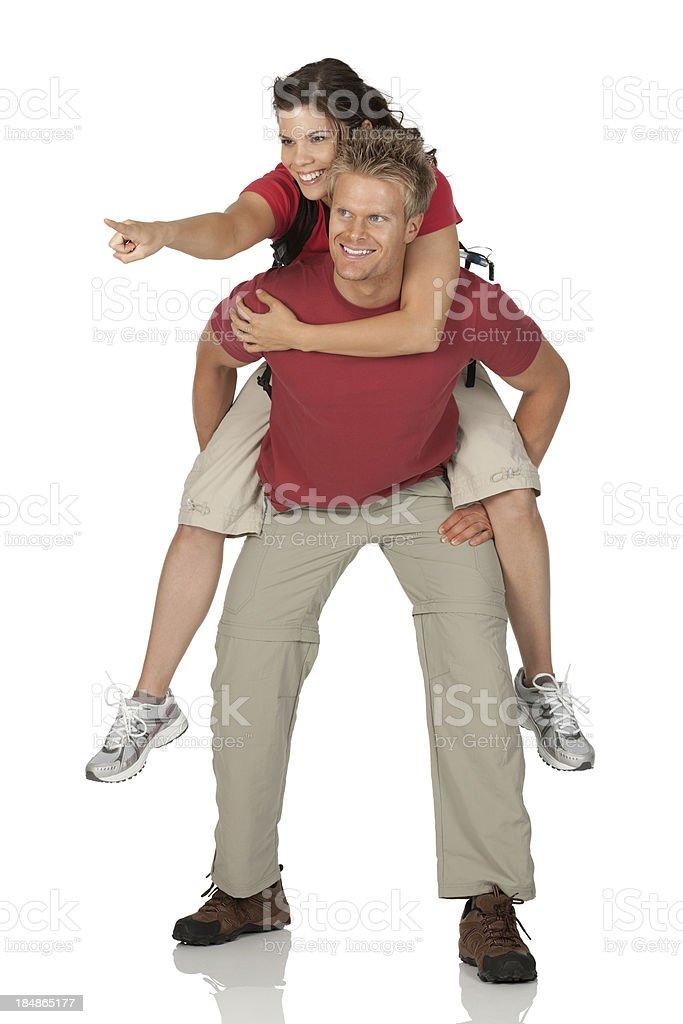 Woman riding piggyback on her boyfriend pointing forward royalty-free stock photo