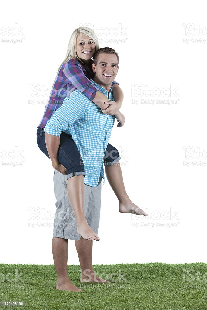 Woman riding piggyback on his boyfriend royalty-free stock photo
