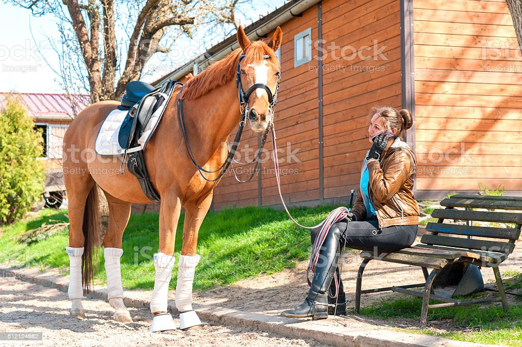 Woman riding trainer near chestnut horse speaking on mobile phone stock photo