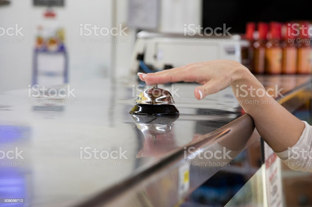 Woman ringing bell in grocery store stock photo