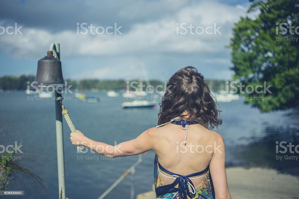 Woman ringing bell to call boatman stock photo