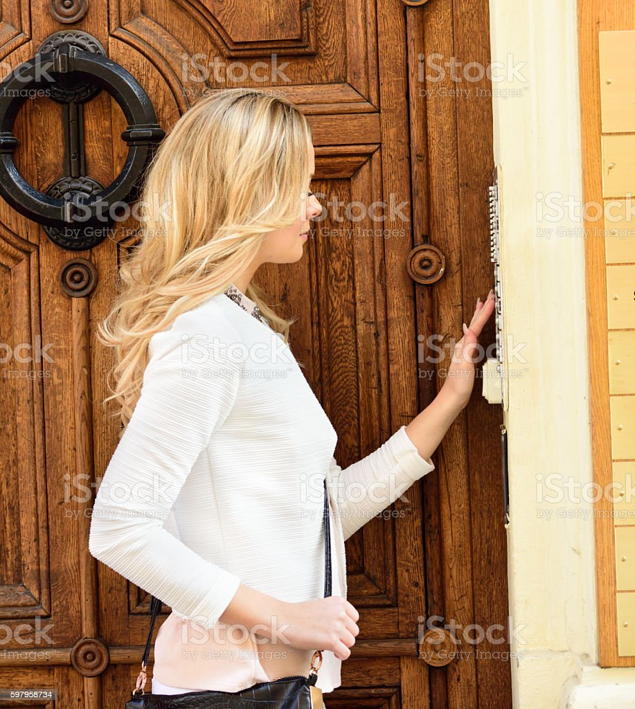 Woman ringing door bell apartment building stock photo