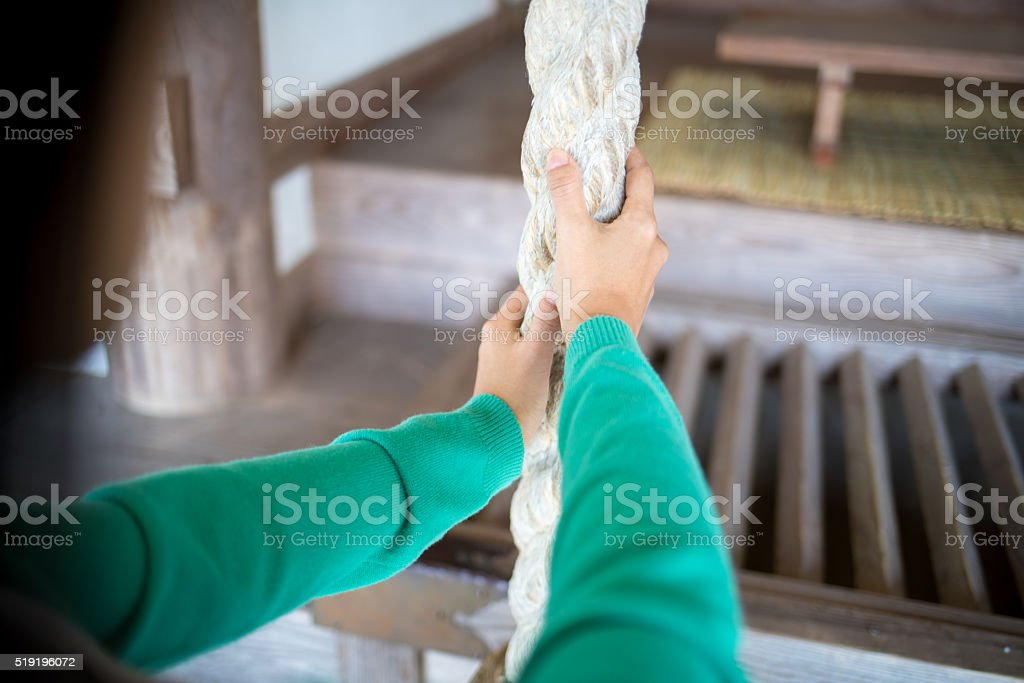 POV of woman ringing the bell at a Japanese temple stock photo
