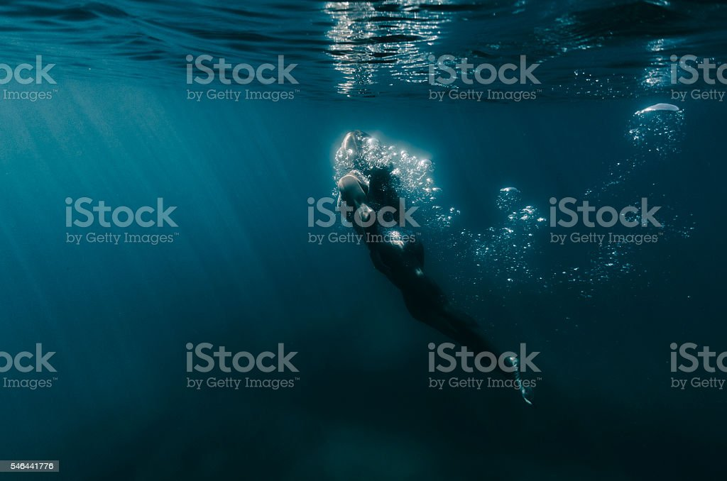Woman rising from the dark waters to the surface stock photo