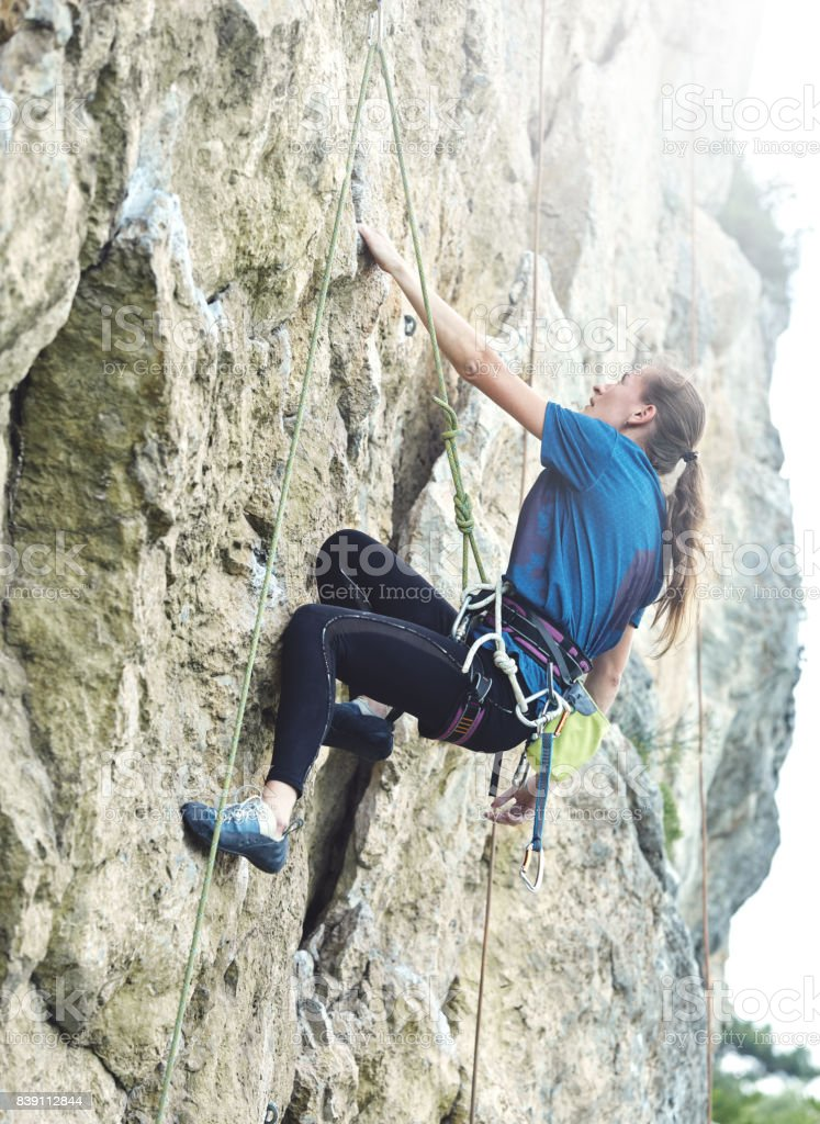 woman rock climber on the cliff stock photo