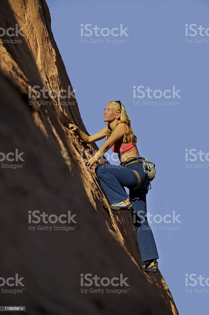 Woman Rock Climbing Against Blue Sky royalty-free stock photo