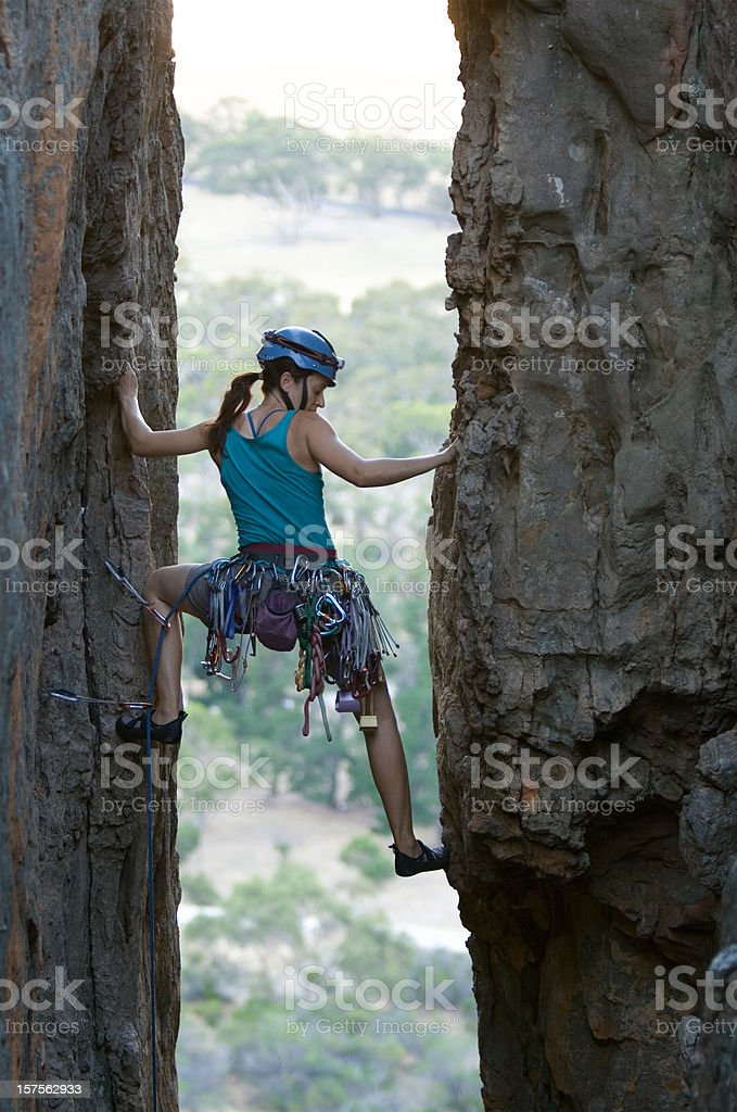 A woman rock climbing outdoors between two rock walls stock photo