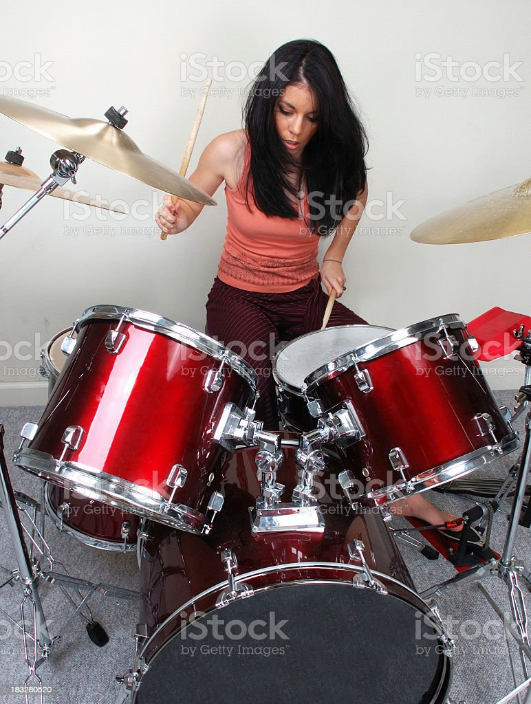 A woman rocking out on a drum set stock photo