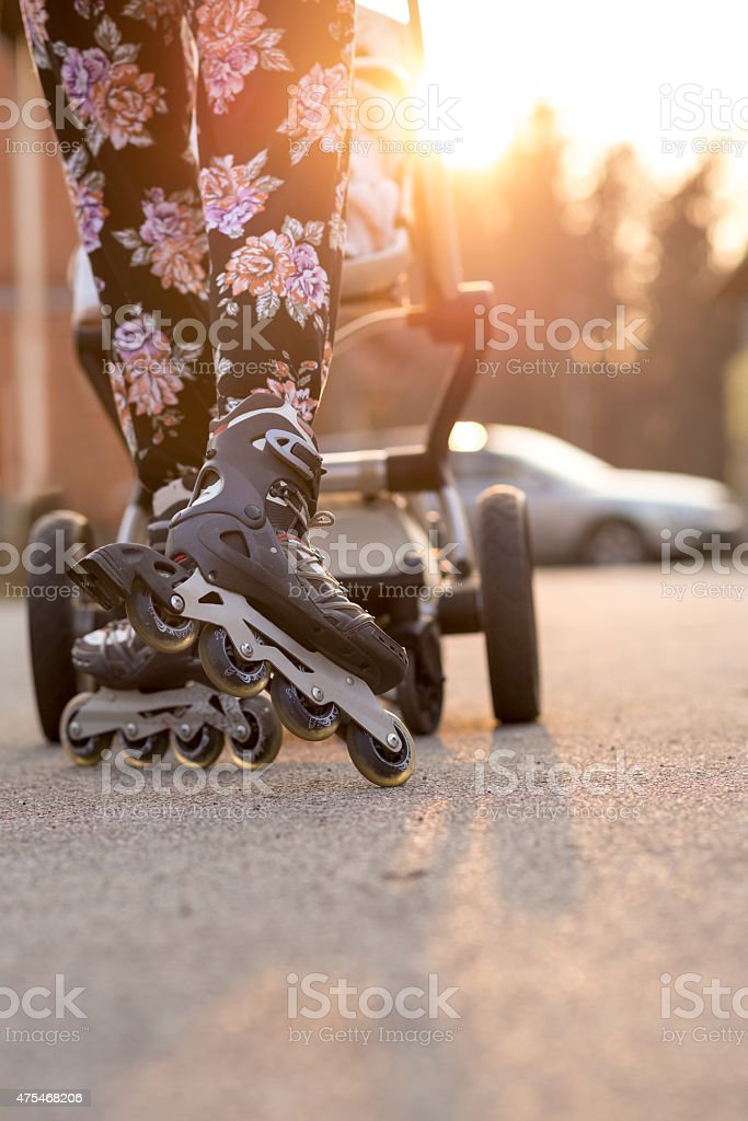 Woman Rollerblading While Pushing Baby Stroller stock photo