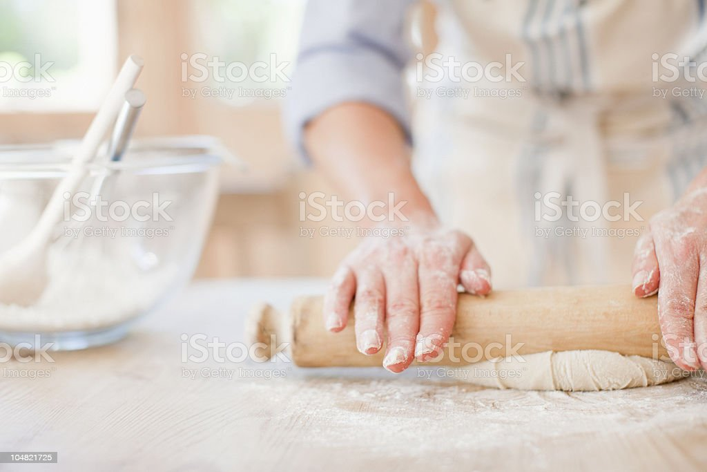 Woman rolling dough with rolling pin on kitchen counter royalty-free stock photo