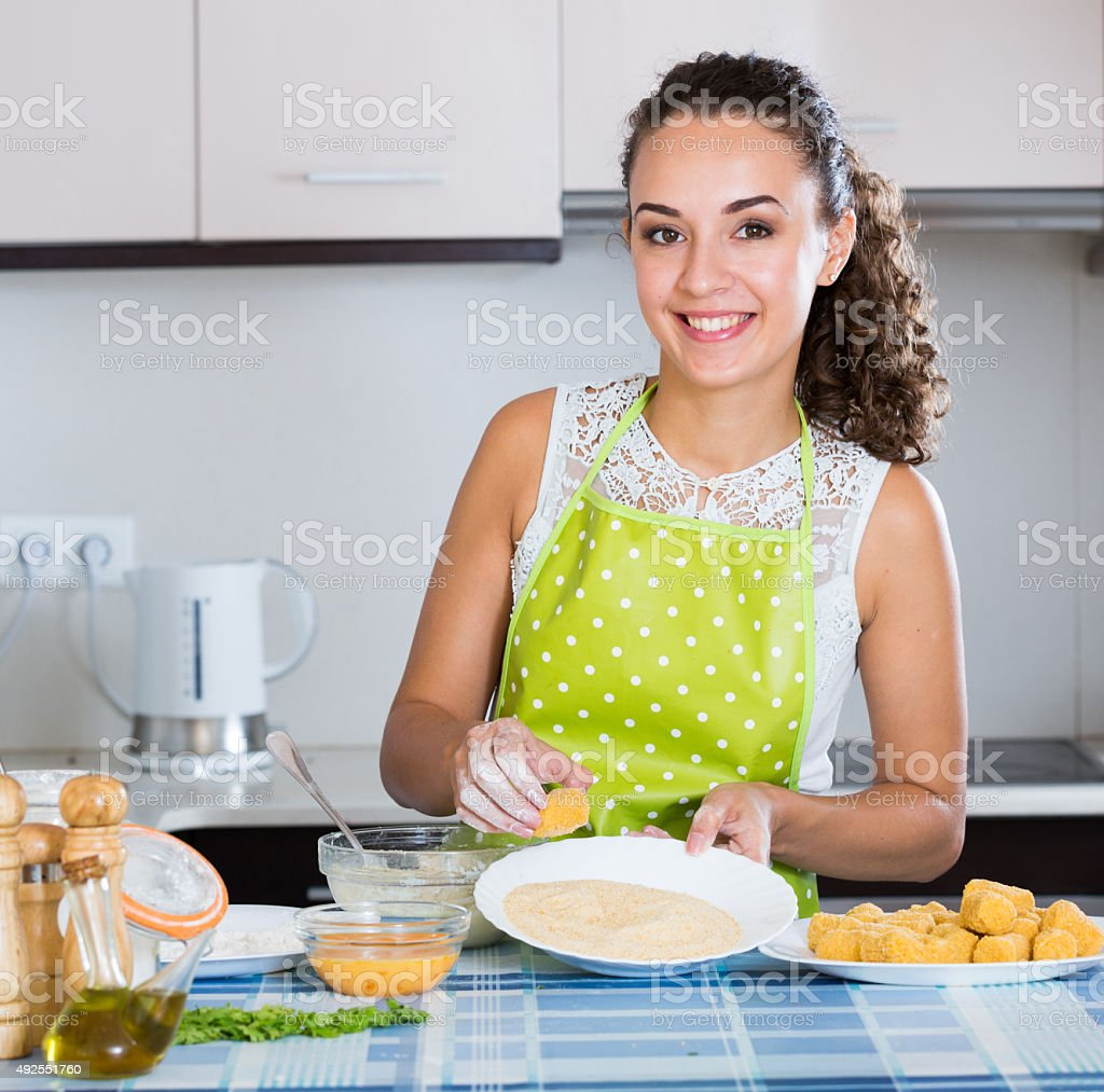 woman rolling filled croquettes stock photo