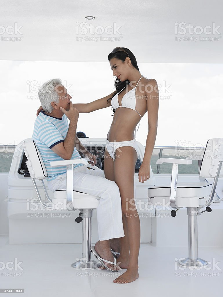Woman Romancing With Man At Helm Of Yacht stock photo