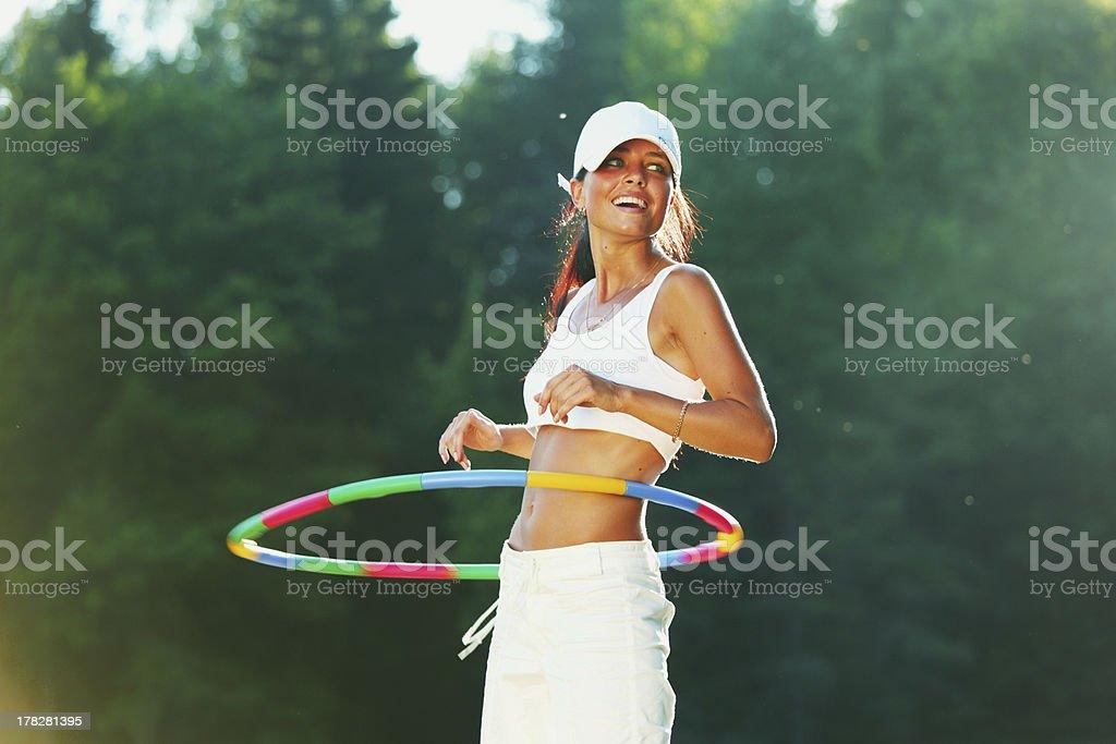 woman rotates hula hoop on nature background stock photo