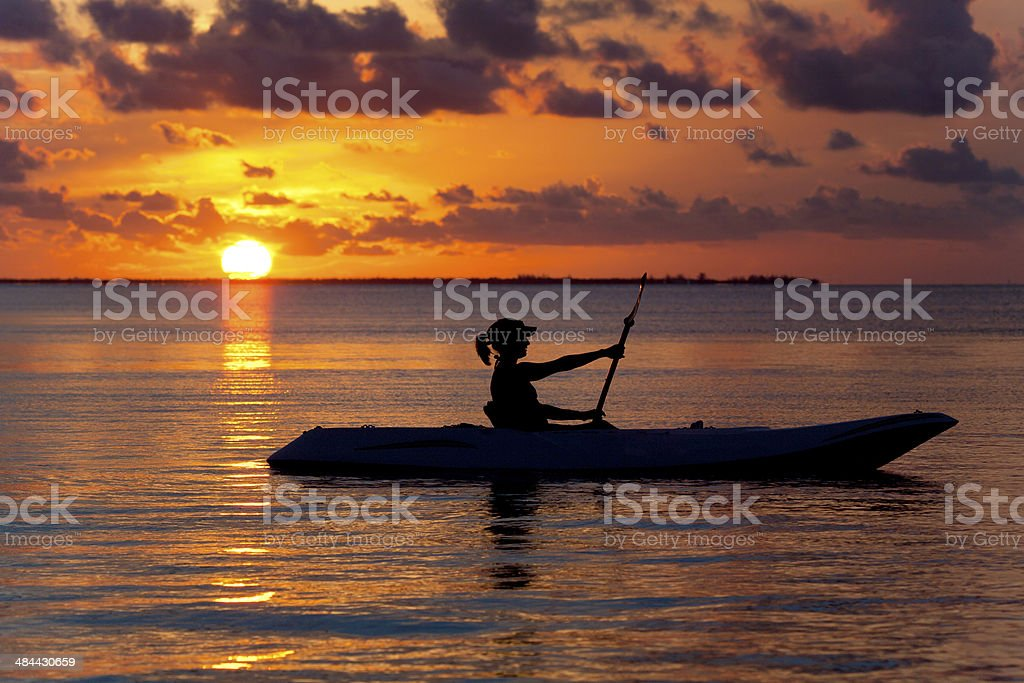 woman rowing and enjoying golden sunset in Florida Keys stock photo