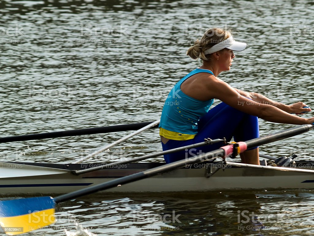 A woman rowing by herself in water stock photo