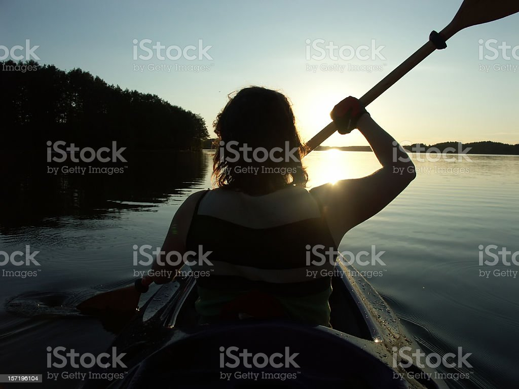 A woman rowing in a canoe on the water royalty-free stock photo