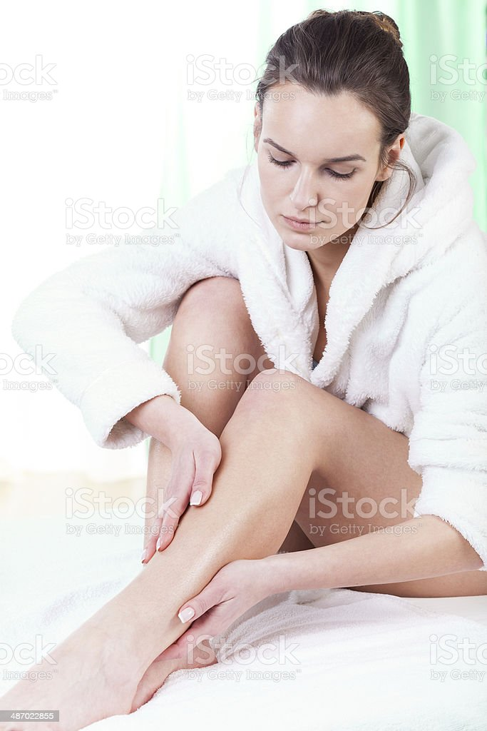 Woman rubbing lotion on her legs stock photo