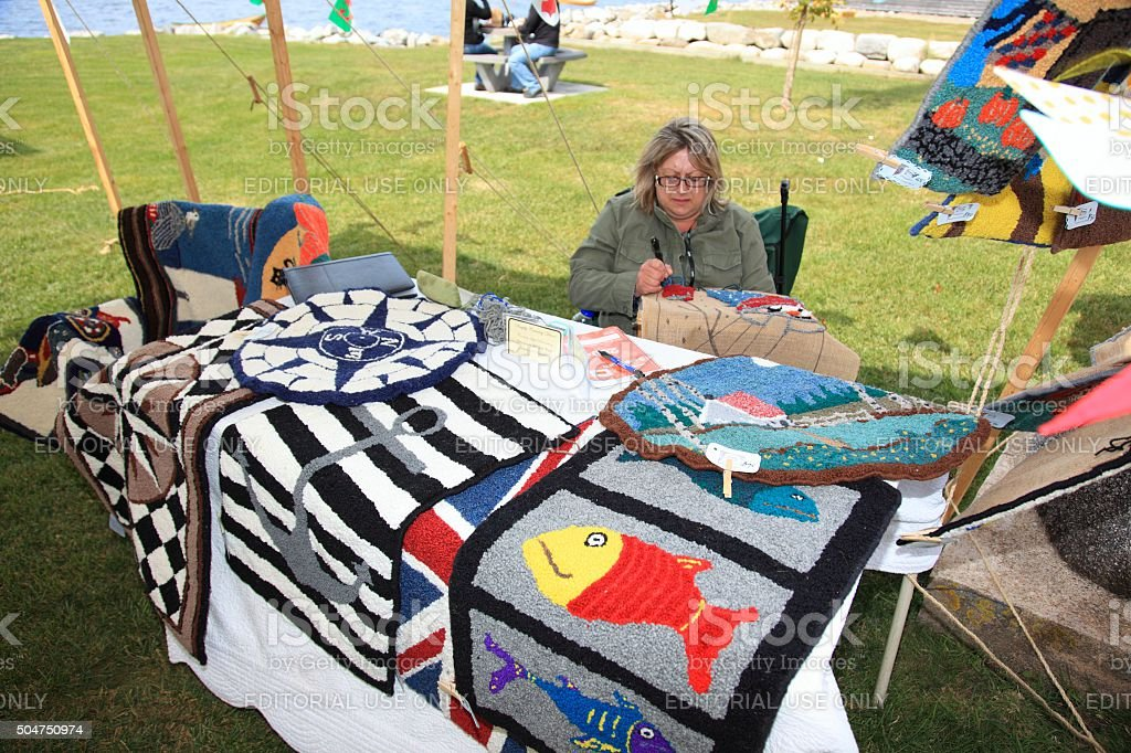 Woman rug hooking at the whirligig festival stock photo