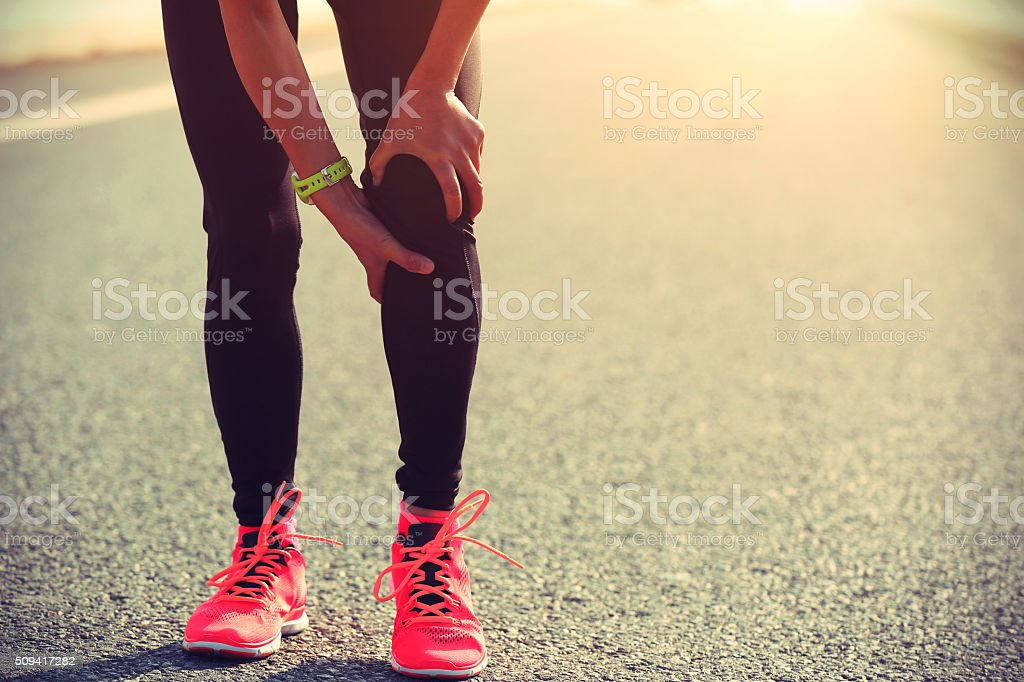woman runner hold her injured leg on road royalty-free stock photo