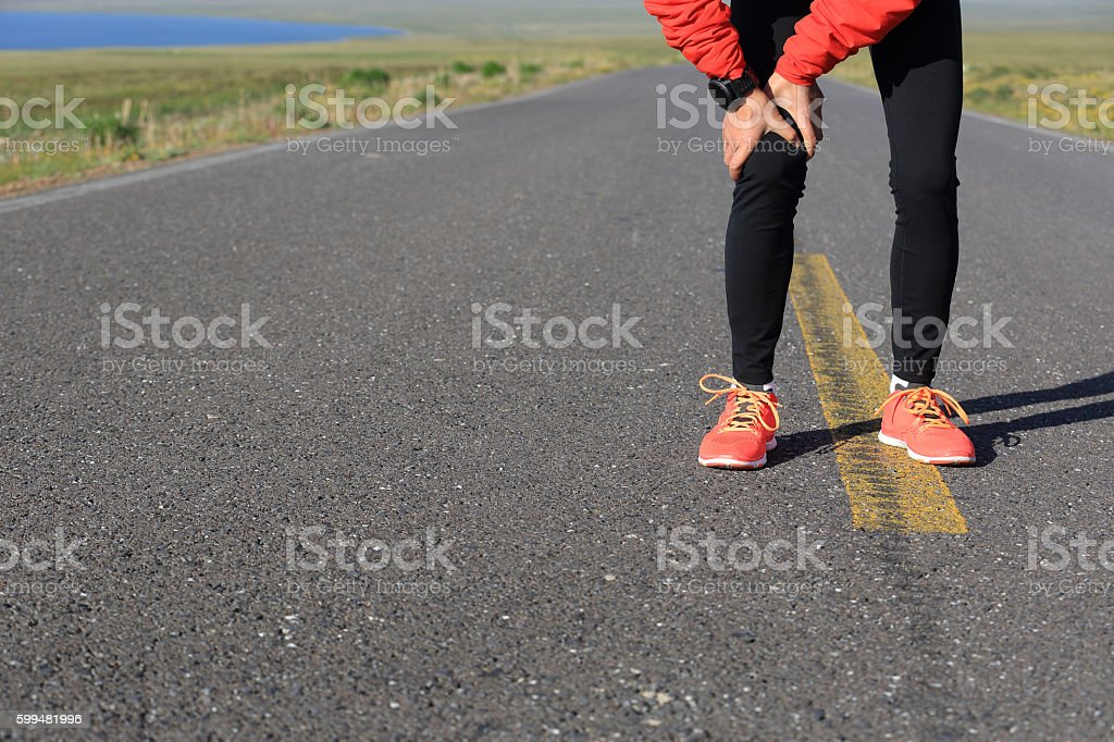 woman runner hold her injured leg on road stock photo