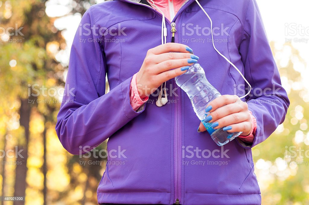 Woman runner holding a bottle of water after running stock photo