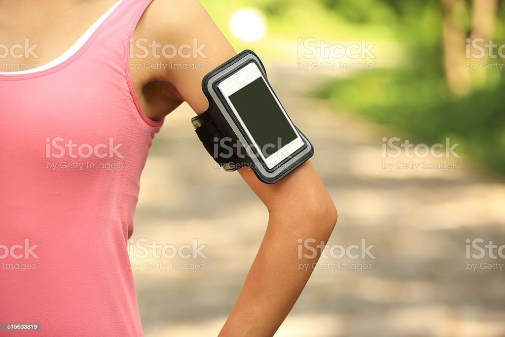 woman runner  listening to music from smart phone mp3 player stock photo