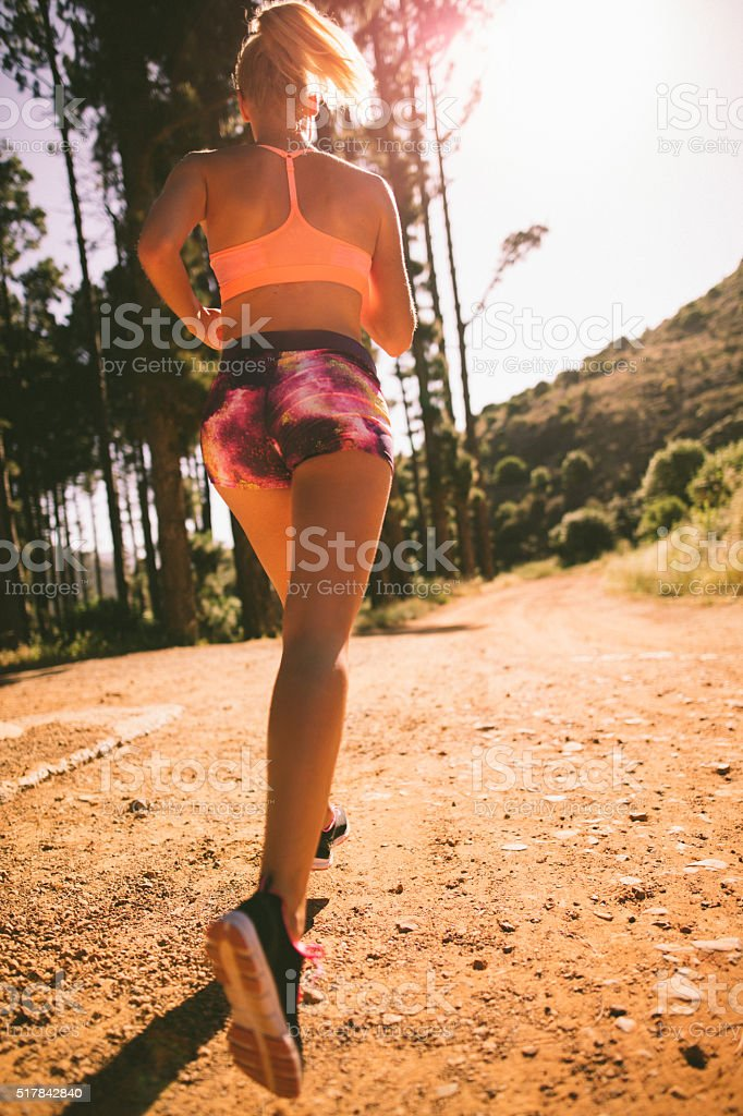 Woman runner on wide dirt road on nature trail run stock photo