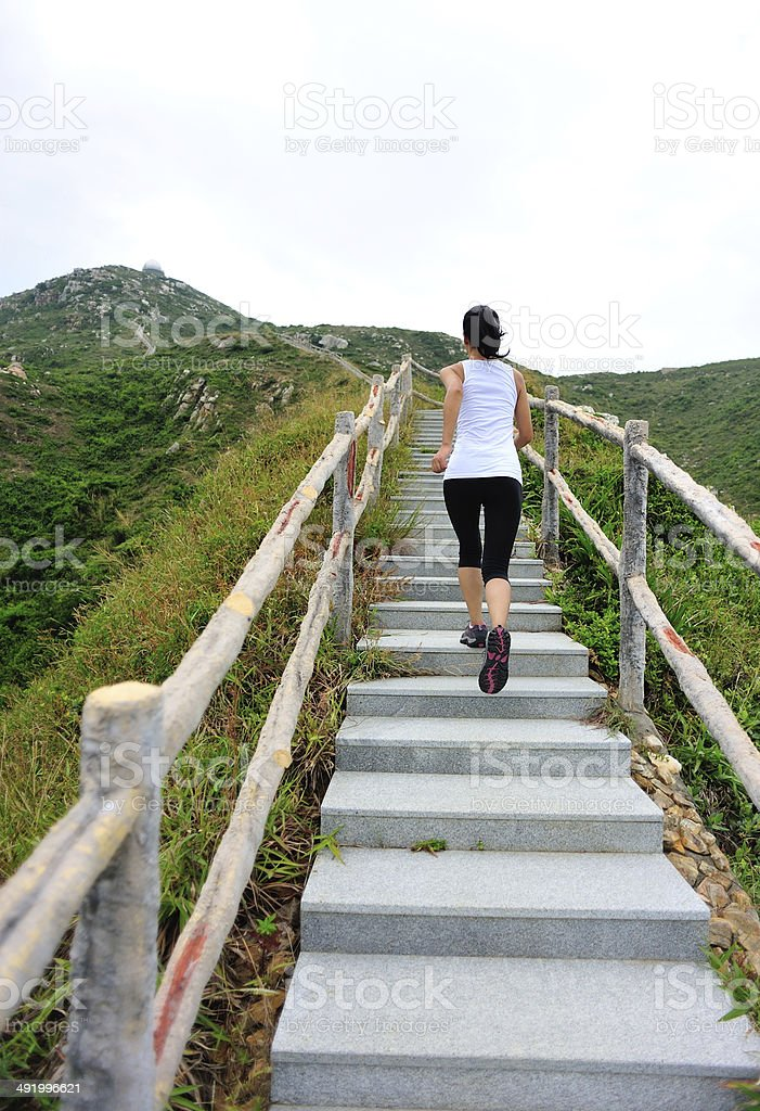 woman runner running at mountain stairs stock photo