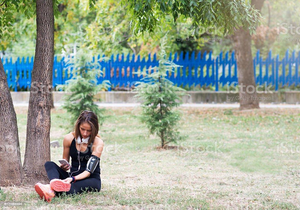 Woman runner sharing running data on social media after exercise. stock photo