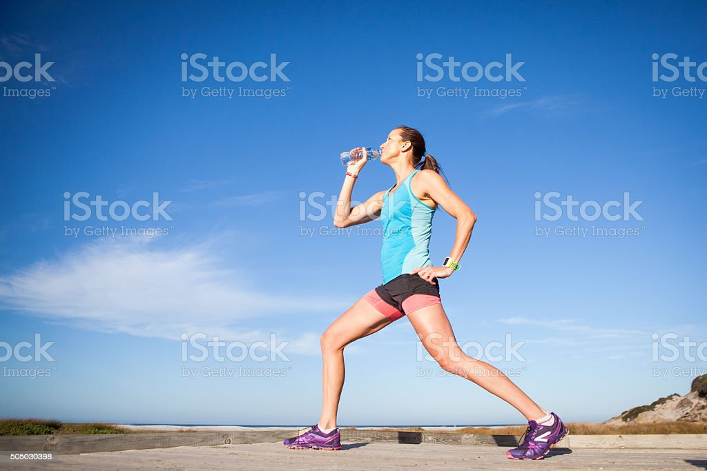 Woman runner stretching and drinking water stock photo