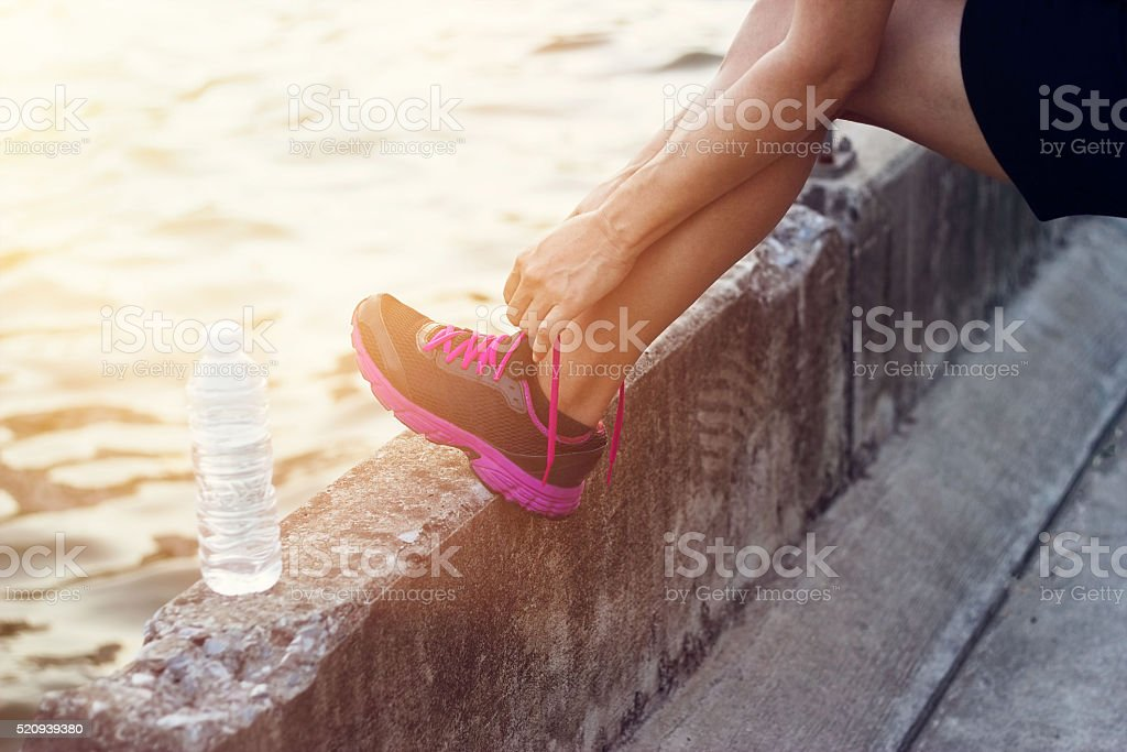 woman runner tying shoelaces on canal background stock photo
