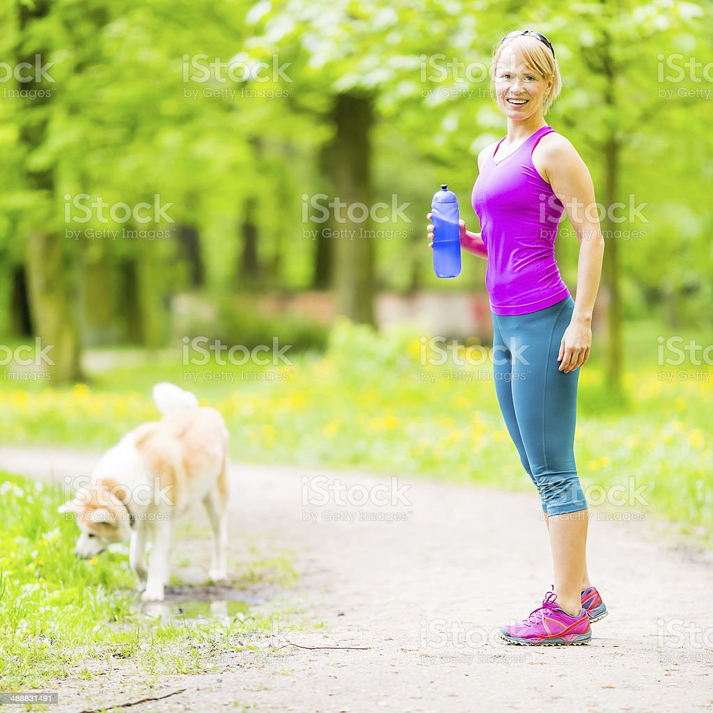Woman runner walking with dog in summer park stock photo
