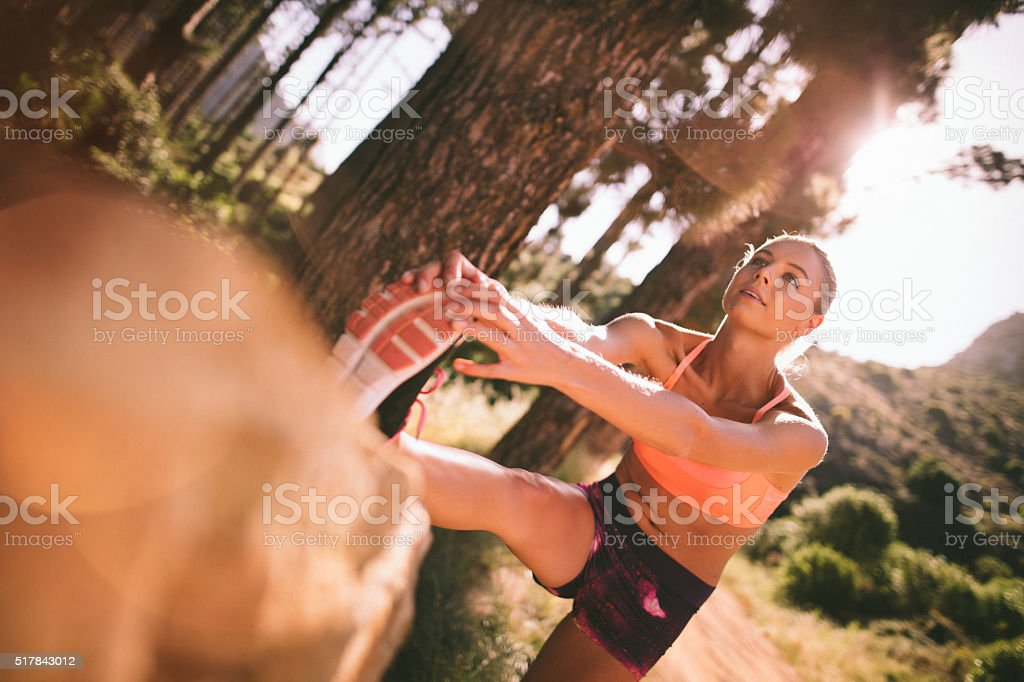 Woman runner warming up on a morning mountain nature trail stock photo