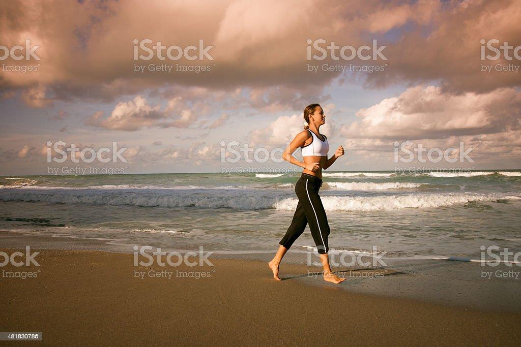 woman running along beach shoreline in Florida, USA stock photo