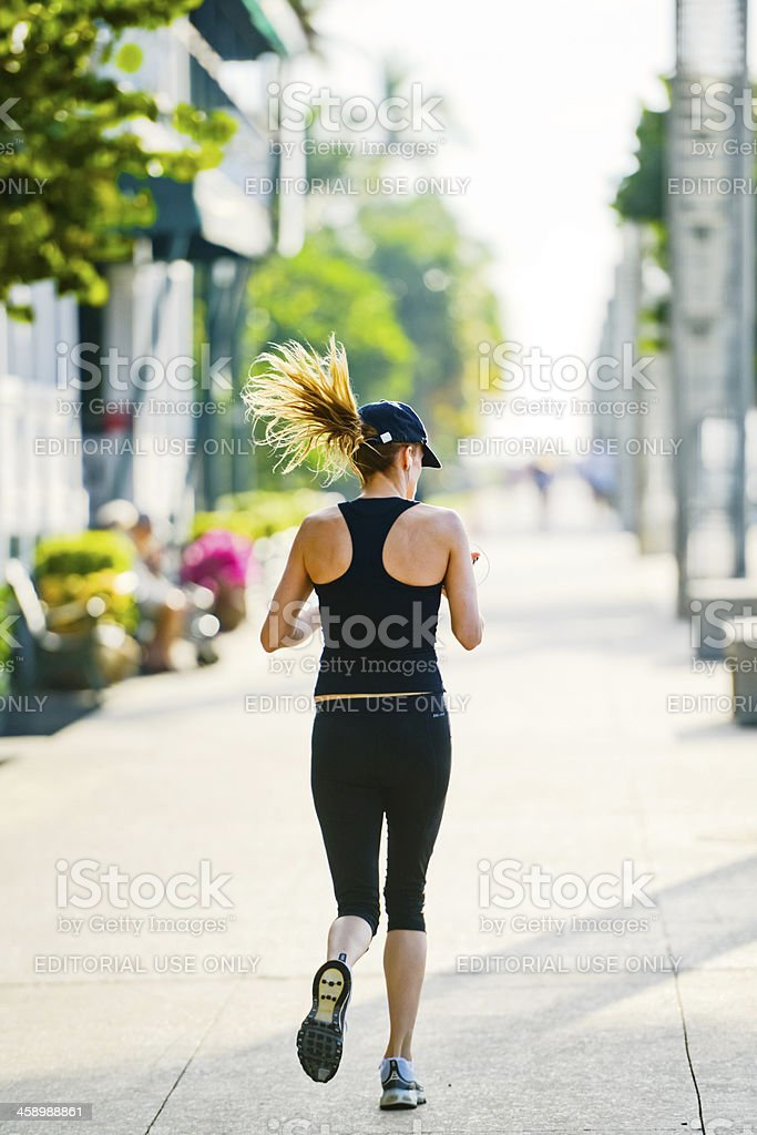 Woman running along the beach and checking her mobile phone royalty-free stock photo