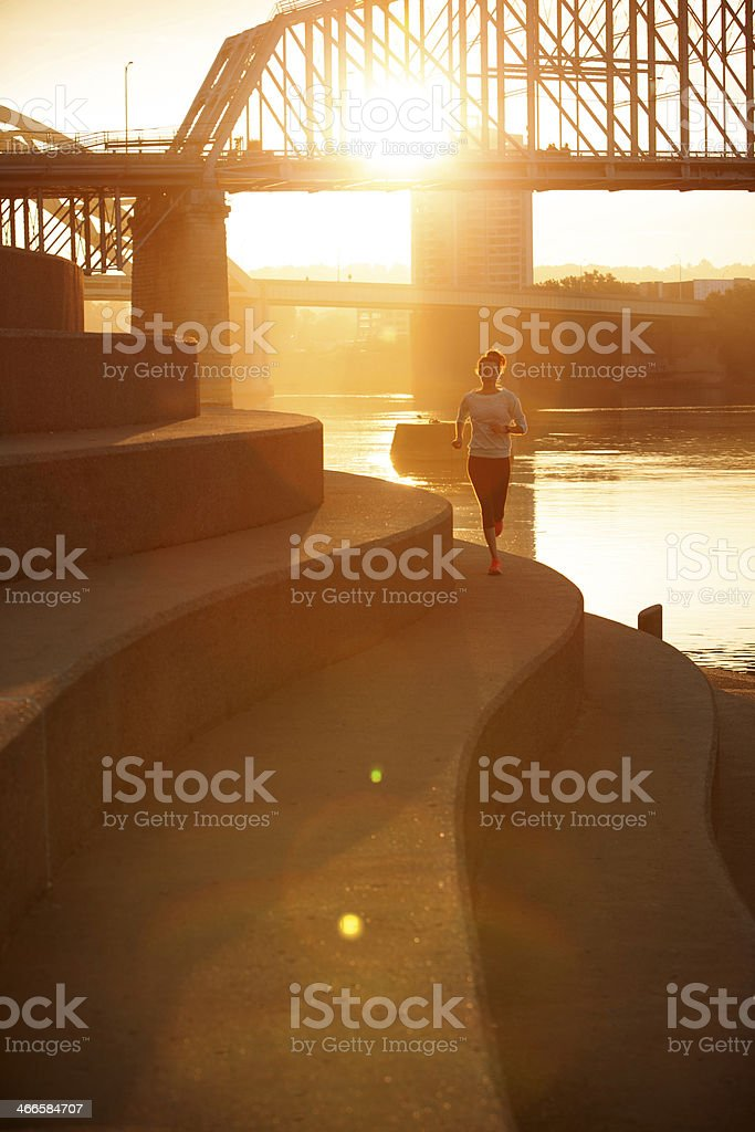 A woman running along the Ohio River during sunrise stock photo