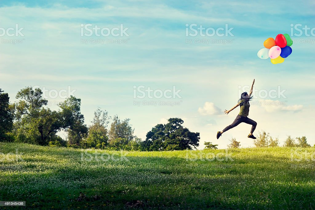 woman running and jumping touch balloons floating in the sky stock photo