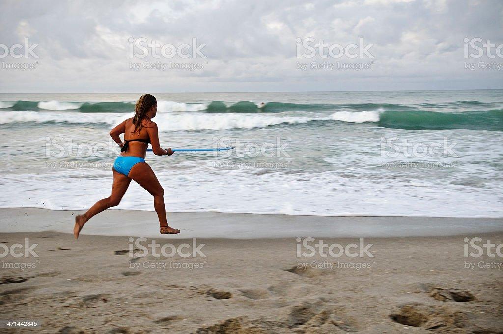 Woman running at beach with skimboard stock photo