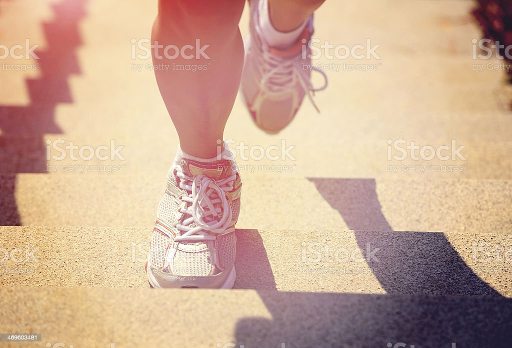 woman running at mountain stairs stock photo