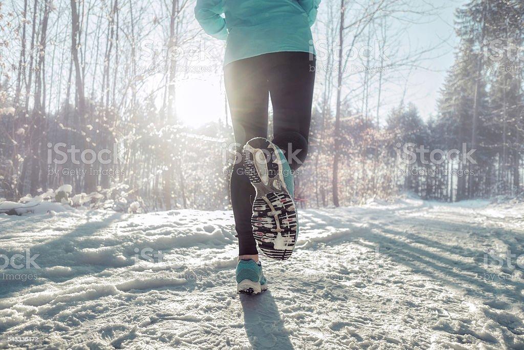 Woman Running at snowly winter under sunlight. stock photo